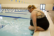 Gabi Jones slips into the swimming pool at the Wheat Ridge recreation center in a suburb of Denver April 14, 2010.  Jones (not her real name) at 502 pounds is an advocate of size acceptance and wants people to know that many large people are very active and healthy as she is by swimming multiple times a week.  REUTERS/Rick Wilking  (UNITED STATES)