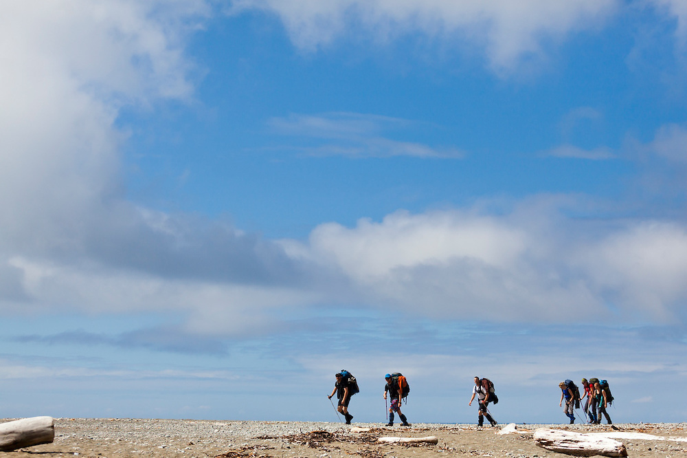 Hikers walk on the beach along the West Coast Trail, British Columbia, Canada.