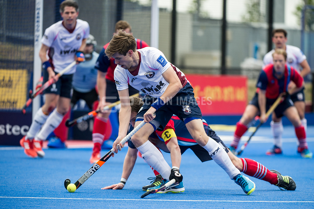Wimbledon's Chris Gregg is watched by Toby Roche of Hampstead & Westminster. Wimbledon v Hampstead & Westminster - Semi-Final - Men's Hockey League Finals, Lee Valley Hockey & Tennis Centre, London, UK on 22 April 2017. Photo: Simon Parker