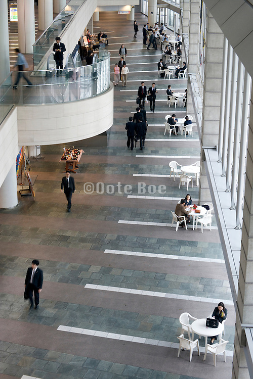 businessmen walking through a large open atrium