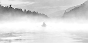 A lone rower cuts through the morning mist  and heads for shore on Lake Watoga.