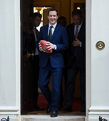 © Licensed to London News Pictures. 02/10/2015. London, UK. British chancellor GEORGE OSBORNE holding an american football as he leaves 11 Downing Street with with NFL stars DAN MARNO and CURTIS MARTIN following a meeting with NFL team owners, execs and former stars ahead of this weekend NFL game at Wembley stadium.  Photo credit: Ben Cawthra/LNP