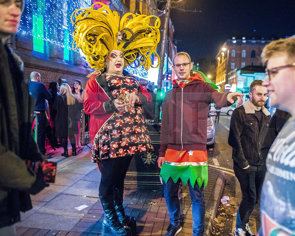 "© Licensed to London News Pictures . 15/12/2017. Manchester, UK. A club promoter wearing drag hands out flyers to passing revellers wearing Christmas costumes . Revellers out in Manchester City Centre overnight during "" Mad Friday "" , named for historically being one of the busiest nights of the year for the emergency services in the UK . Photo credit: Joel Goodman/LNP"