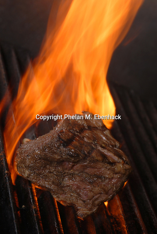 A Filet Mignon Steak cooks on a flaming grill at a restaurant in Orlando, Florida.