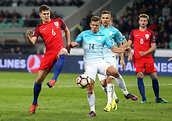 John Stones of England and Roman Bezjak of Slovenia challenge for the ball - Mandatory by-line: Robbie Stephenson/JMP - 11/10/2016 - FOOTBALL - RSC Stozice - Ljubljana, England - Slovenia v England - World Cup European Qualifier