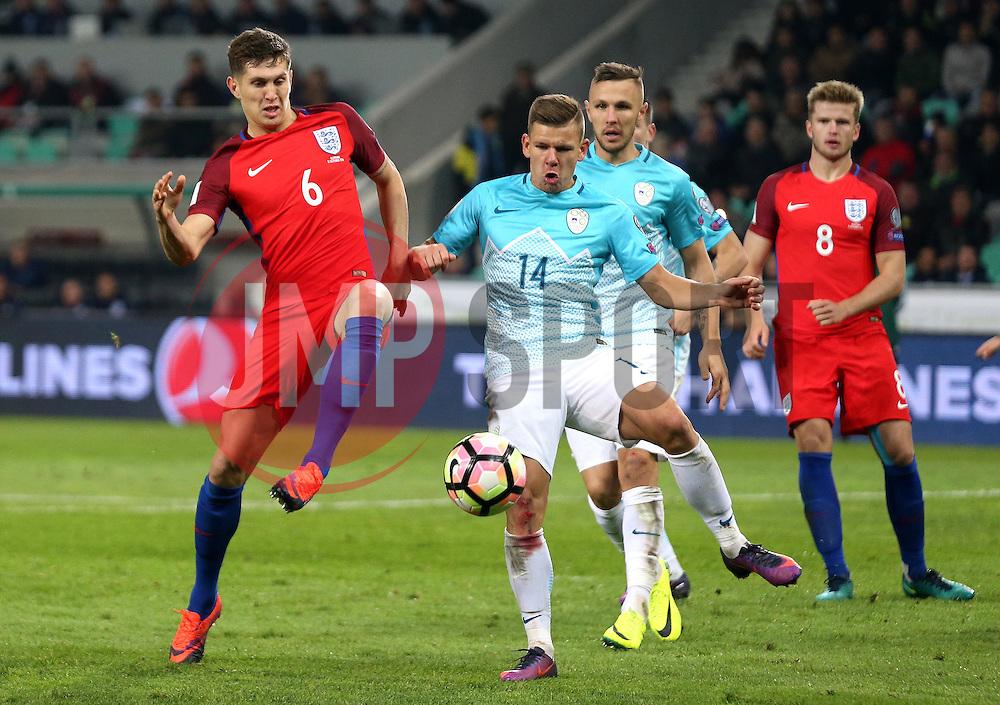 John Stones of England and Roman Bezjak of Slovenia challenge for the ball - Mandatory by-line: Robbie Stephenson/JMP - 11/10/2016 - FOOTBALL - RSC Stozice - Ljubljana, England - Slovenia v England - World Cup European Qualifier