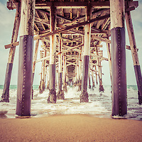 Under the pier in Orange County California picture of the wooden posts that support Balboa Pier. Balboa Pier is on Balboa Peninsula in Newport Beach, Orange County, California. Photo has a vintage 1950s tone.