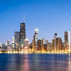 Photo of Chicago skyline at twilight. Includes the John Hancock Center building and other popular downtown Chicago city buildings at dusk. The John Hancock Center is one of the world's tallest skyscrapers and is a famous fixture in the Chicago skyline.