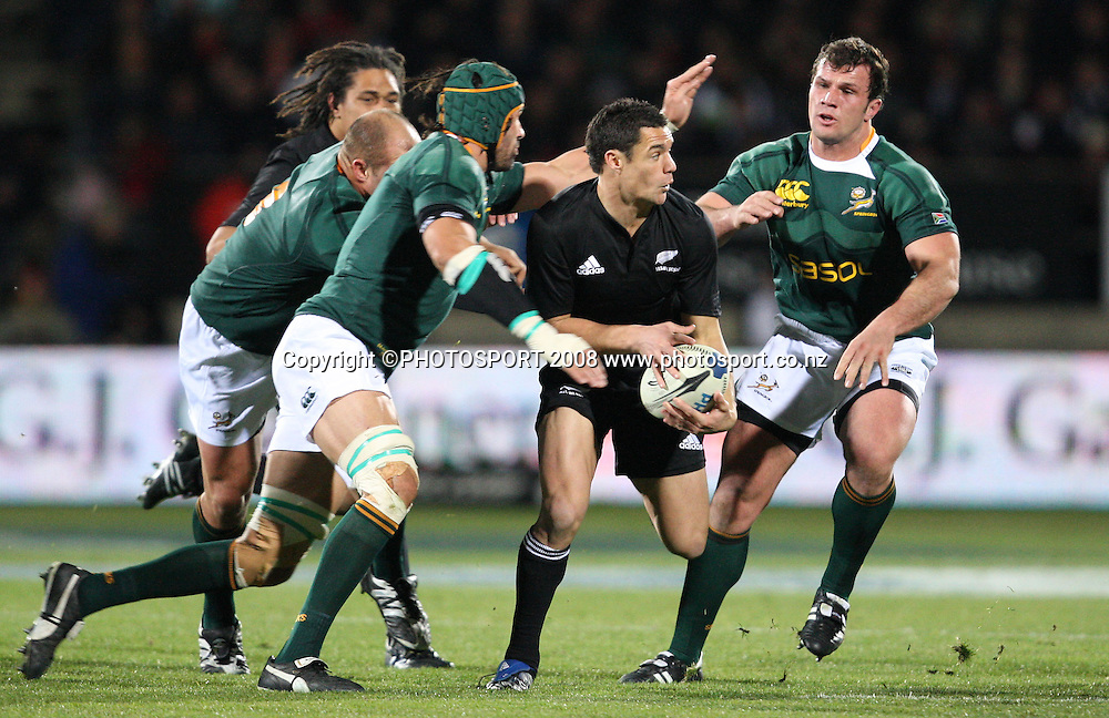 Dan Carter looks for his support before he is swamped by South African defence.<br />