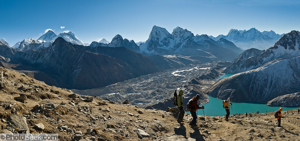 Trekkers view Mount Everest on Gokyo Ri above Third Gokyo Lake (Dudh Pokhari) in the Himalaya Mountains of Nepal, Asia. See Mount Everest (left), adjacent Lhotse, the distant pyramid of Makalu, and prominent center peak Arakam Tse with Cholatse. The largest glacier in Nepal, Ngozumpa Glacier, flows down the valley floor covered in gray rocks. Its lateral moraine dams several lakes. Sagarmatha National Park was created in 1976 and honored as a UNESCO World Heritage Site in 1979. Published in Wilderness Travel Catalog of Adventures 2013. Panorama stitched from 3 images.