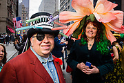 New York, NY - 21 April 2019. A woman with a giant flower for a hat and a man with a hat dressed in colorful mechanical springs, self-descrived as the latest in spring fashion,  at the Easter Bonnet Parade and Festival on New York's Fifth Avenue.