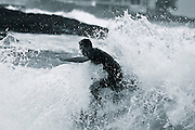 action shot: surfer showing courage as he is engulfed by crashing wave at Kona Reef, Kona, Hawaii presented in monochromatic tones