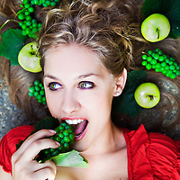 Blonde girl laying on the ground, biting grapes