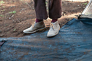 A porter named John carries his load everyday wearing his favorite purple socks. His pants are ill-fitting and his shoes are meant more for city streets.