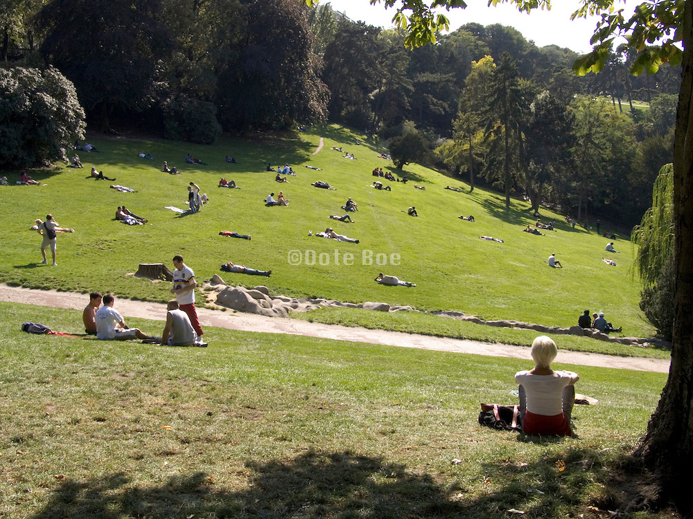 people lying and sitting on the grass in a park Paris