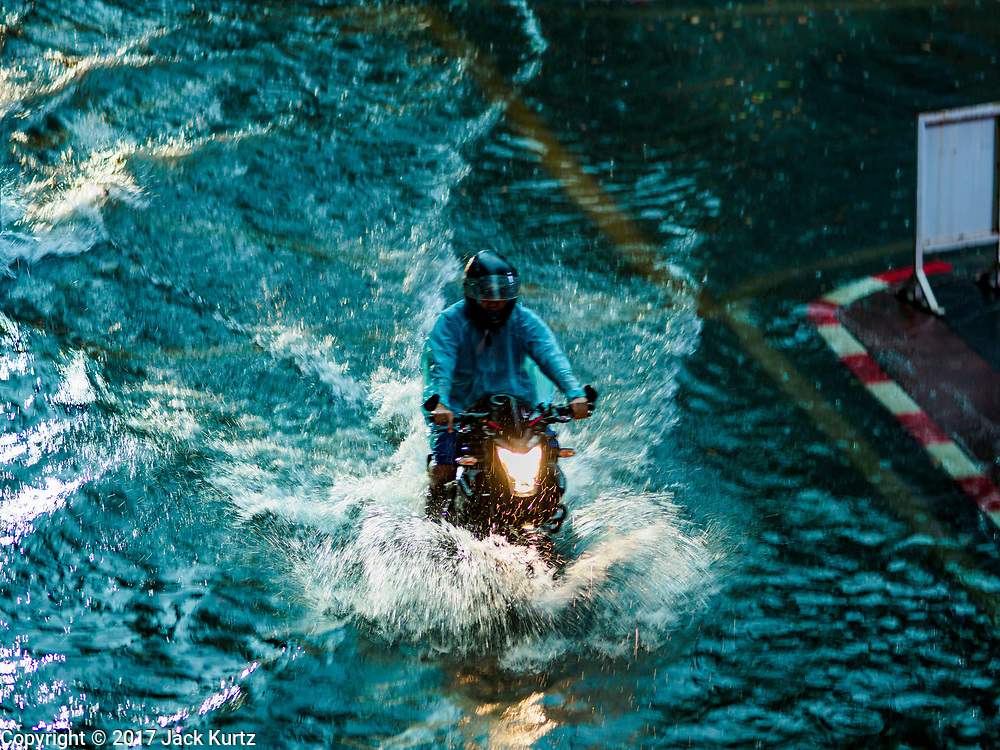 27 MAY 2017 - BANGKOK, THAILAND: A motorcycle on Rama I Street, which was flooded by monsoonal rains. The rainy season in Bangkok usually starts in mid-June but started almost a month early this year. There have been daily thunderstorms and localized flooding throughout central Thailand since the middle of May.     PHOTO BY JACK KURTZ