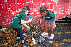 All Saints volunteers Kaylyn Bryan, left,  and Shadae Caines help with the cleanup.  Residents and volunteers gather for the Garden Street neighborhood cleanup and block Party hosted by E's Garden and Things, Long Path/Garden Street Community Association, and the Economic Development Authority's Enterprise and Commerical Zone Commission.  St. Thomas, USVI.  5 September 2015.  © Aisha-Zakiya Boyd