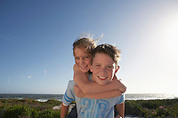 Boy giving girl piggyback in front of ocean half length