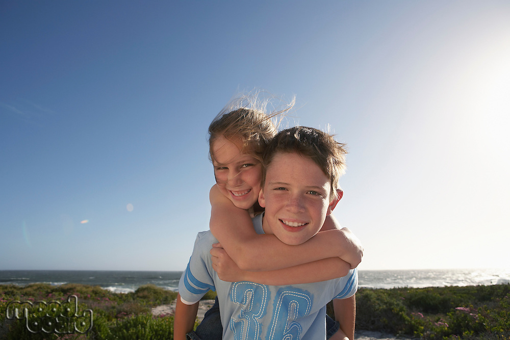 Boy giving girl piggyback in front of ocean half length