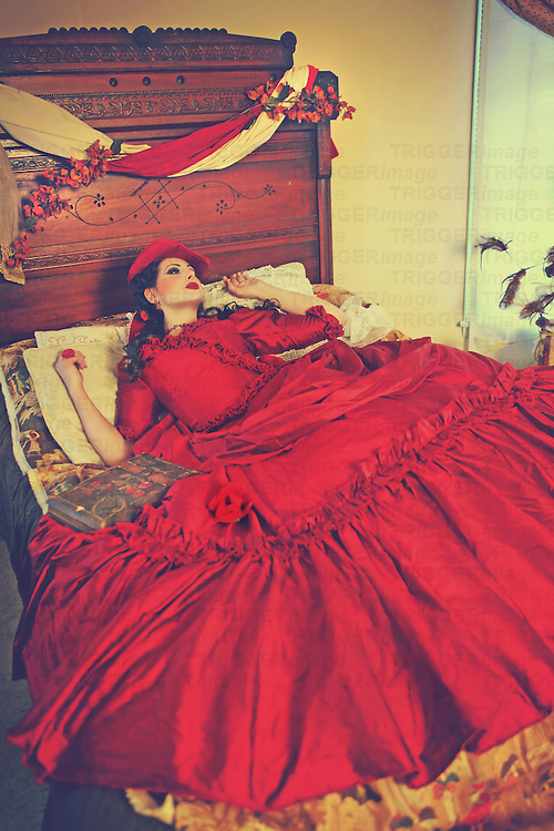 Young woman in a beautiful fancy red gown laying sadly in a large Victorian bed