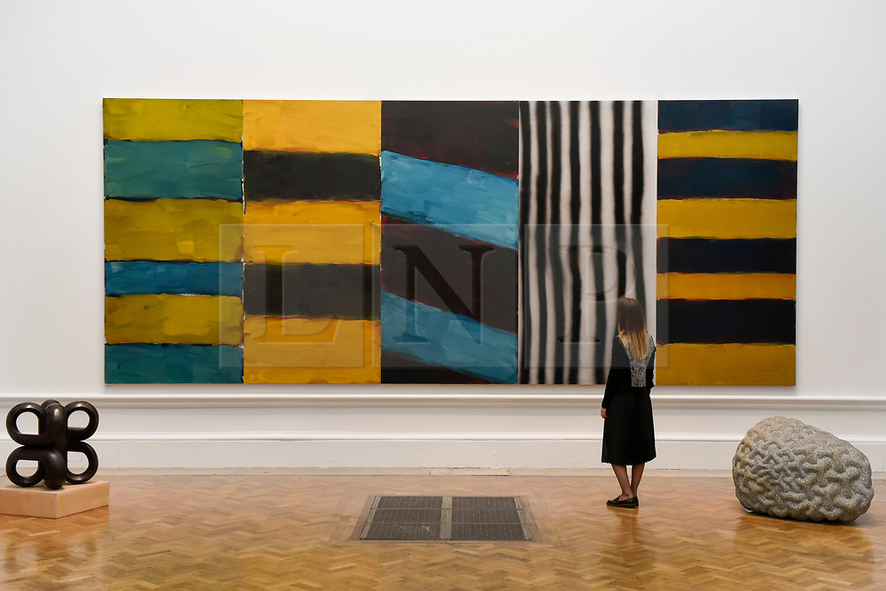 """© Licensed to London News Pictures. 08/06/2017. London, UK. A visitor views """"Full House"""" by Sean Scully RA, which is hung between two sculptures (L to R) """"Volute IV"""" by Paul de Monchaux and """"Warp and Woof"""" by Peter Randall-Page RA. Preview of the Summer Exhibition 2017 at the Royal Academy of Arts in Piccadilly.  Co-ordinated by Royal Academician Eileen Cooper, the 249th Summer Exhibition is the world's largest open submission exhibition with around 1,100 works on display by high profile and up and coming artists.<br />  Photo credit : Stephen Chung/LNP"""