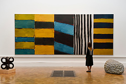 &copy; Licensed to London News Pictures. 08/06/2017. London, UK. A visitor views &quot;Full House&quot; by Sean Scully RA, which is hung between two sculptures (L to R) &quot;Volute IV&quot; by Paul de Monchaux and &quot;Warp and Woof&quot; by Peter Randall-Page RA. Preview of the Summer Exhibition 2017 at the Royal Academy of Arts in Piccadilly.  Co-ordinated by Royal Academician Eileen Cooper, the 249th Summer Exhibition is the world's largest open submission exhibition with around 1,100 works on display by high profile and up and coming artists.<br />  Photo credit : Stephen Chung/LNP