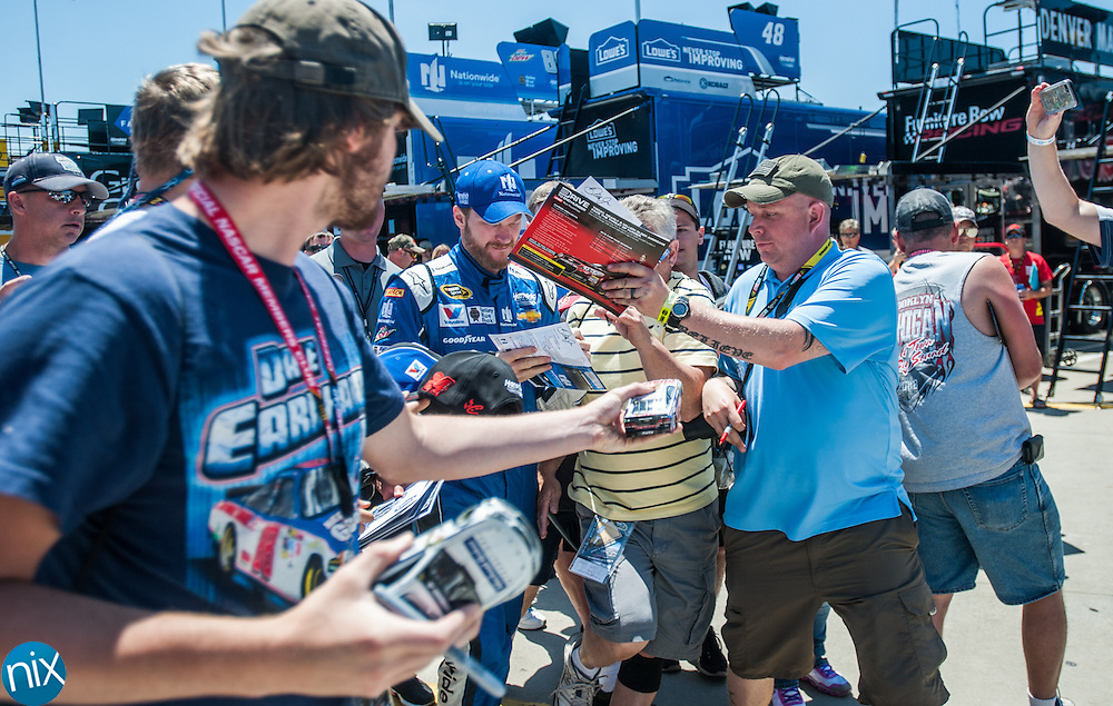 Race fans seek autographs from Dale Earnhardt Jr. as he walks to his car for the final practice for the Coca-Cola 600 Saturday afternoon at Charlotte Motor Speedway.