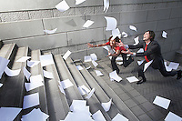 Busines man and woman catching falling paperwork on steps