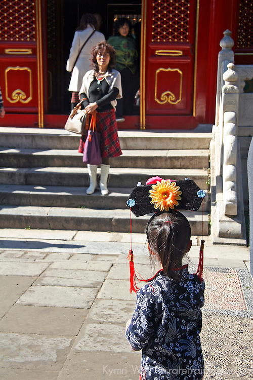 Asia, China, Beijing. A young girl in traditional Chinese dress and hat at the Forbidden Palace.