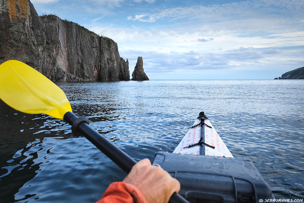 First person point of view while sea kayaking along the dramatic, rocky coast of Trinity Bay Newfoundland, Canada