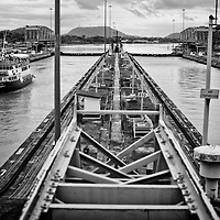 MIRAFLORES LOCKS - PANAMA CANAL<br /> Photography by Aaron Sosa<br /> Panama City, Panama 2012<br /> (Copyright © Aaron Sosa)<br /> <br /> The Panama Canal is an 77.1-kilometre (48 mi) ship canal in Panama that connects the Atlantic Ocean (via the Caribbean Sea) to the Pacific Ocean. The canal cuts across the Isthmus of Panama and is a key conduit for international maritime trade. There are locks at each end to lift ships up to Lake Gatun (26m (85ft) above sea-level) which was used to reduce the amount of work required for a sea-level connection. The current locks are 33.5m (110ft) wide although new larger ones are proposed.<br /> <br /> Work on the canal, which began in 1881, was completed in 1914, making it no longer necessary for ships to sail the lengthy Cape Horn route around the southernmost tip of South America (via the Drake Passage) or to navigate the dangerous waters of the Strait of Magellan. One of the largest and most difficult engineering projects ever undertaken, the Panama Canal shortcut made it possible for ships to travel between the Atlantic and Pacific Oceans in half the time previously required. The shorter, faster, safer route to the U.S. West Coast and to nations in and along the Pacific Ocean allowed those places to become more integrated with the world economy.