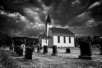 Dark rolling clouds hover above a white wooden clapboard church near Oak Bay in rural Quebec, Canada. Dark gravestones, stand in the churchyard in front of the church.