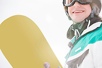 Smiling young man holding snowboard