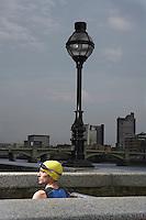 Athlete standing between river embankment ledges London England