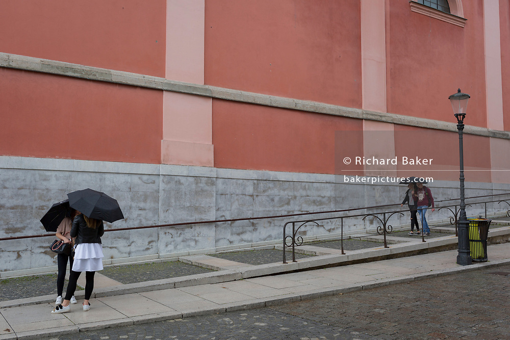 Friends talk in the rain at the bottom of steps on Miklosiceva Cesta (street) in the Slovenian capital, Ljubljana, on 28th June 2018, in Ljubljana, Slovenia.