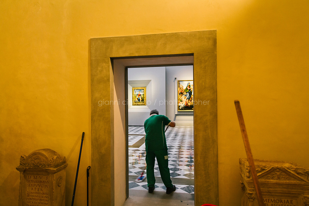 FLORENCE, ITALY - 4 JUNE 2018: A janitor wipes the floow of room 41, dedicated to Raphael and Michelangelo, before the inauguration at the Uffizi, in Florence, Italy, on June 4th 2018.<br /> <br /> As of Monday June 4th 2018, Room 41 or the &ldquo;Raphael and Michelangelo room&rdquo; of the Uffizi is part of the rearrangement of the museum's collection that has<br /> been defining Uffizi Director Eike Schmidt&rsquo;s grander vision for the Florentine museum.<br /> Next month, the museum&rsquo;s Leonardo three paintings will be installed in a<br /> nearby room. Together, these artists capture &ldquo;a magic moment in the<br /> first decade of the 16th century when Florence was the cultural and<br /> artistic center of the world,&rdquo; Mr. Schmidt said. Room 41 hosts, among other paintings, the dual portraits of Agnolo Doni and his wife Maddalena Strozzi painted by Raphael round 1504-1505, and the &ldquo;Holy Family&rdquo;, that Michelangelo painted for the Doni couple a year later, known as the<br /> Doni Tondo.