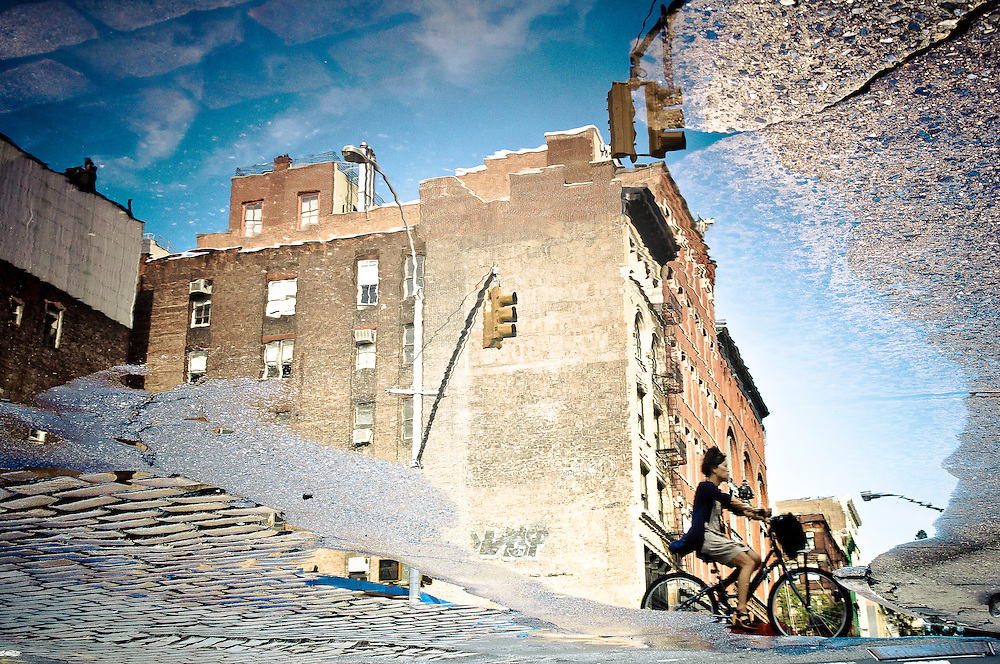 Reflection in a puddle of a woman riding her bike on Grand Street in SoHo, Manhattan, New York, 2010.