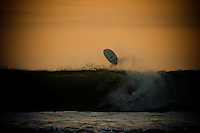 A surfboad is airborne after a surfer succumbs to a wave at Kuta Beach, Bali, Indonesia, Southeast Asia.