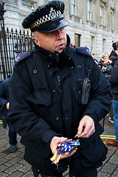 © Licensed to London News Pictures. 08/12/2015. London, UK. Medals thrown down by war veterans picked by police officer outside Downing Street in a protest against the attack on Syria. The protest is organised by Veterans For Peace on Tuesday, 8 December 2015. Photo credit: Tolga Akmen/LNP