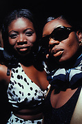 Two black females wearing dresses, one with sunglasses at garage Night, London, U.K, 1998.