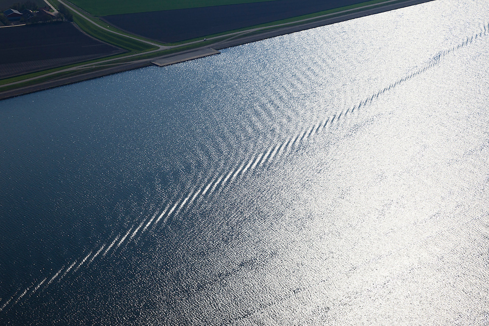 Nederland, Flevoland, Ketelmeer, 01-05-2013; Rimpels vormen spoor van boot in water voor de kust van Flevoland.<br /> The water glistens by the late sunshine on the surface. <br /> luchtfoto (toeslag op standard tarieven)<br /> aerial photo (additional fee required)<br /> copyright foto/photo Siebe Swart