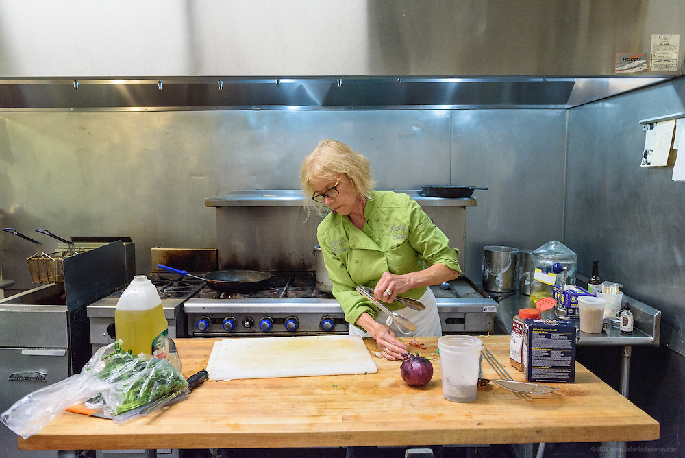 Chef Kathy Cary clears the cutting board to prepare another dish. Lunchtime in the kitchen at Lilly's Monday, Aug. 15, 2016 with Chef/Owner Kathy Cary and staff. (Photo by Brian Bohannon)