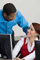 Woman Wearing Headset Chatting with Colleague