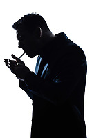 one caucasian man portrait smoking lighting cigarette silhouette in studio isolated white background