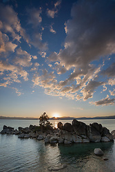 """Sunset at Whale Beach, Tahoe 1"" - Photograph of the sun setting above boulders and a tree at Whale Beach, Lake Tahoe."