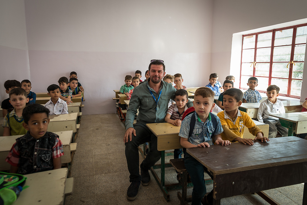 11 October 2017 &ndash; Ninewa Plains &ndash; Iraq &ndash; Engineer Suhaib sits with a class at Al-Taghllubia School for Boys in the Ninewa Plains on the day the school reopened its doors to pupils after being closed for 3 years. <br /> <br /> &ldquo;There was no one here for 3 years after ISIL came,&rdquo; said Principal Jubrail Ibrahim. &ldquo;The students went to Erbil, Duhok, Baghdad, Kirkuk. Today is the first day the pupils came back to their school. It&rsquo;s made us all very happy.&rdquo; UNDP&rsquo;s Funding Facility for Stabilization is helping rehabilitate the school. <br /> <br /> &copy; UNDP Iraq / Claire Thomas