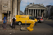 An illusion of yellow traffic bollard seemingly knocked over by a yellow delivery van at Bank Triangle, City of London.