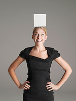 Young woman in black dress with white box on her head