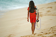 A girl dressed in red walks away with a surfboard n a Hawaiian Beach