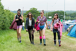 © Licensed to London News Pictures. 12/06/2015. Isle of Wight, UK.  Festival goers walk through the campsite of Isle of Wight Festival 2015 on the morning of Friday Day 2.  Yesterday the weather was hot and Sunny.  Today rain is forecast.  This years festival include headline artists the Prodigy, Blur and Fleetwood Mac.  Photo credit : Richard Isaac/LNP